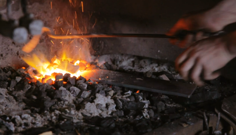 Blacksmith heating steel in a forge